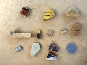 Early colonial artifacts of note recovered from the hot boxes include fragments of bulbous German Westerwald stoneware jugs with rilled necks colored with purple manganese pigment (bottom row, right), Midlands mottled from central England (top row left), dot and combed buff-bodied earthenware attributed to Staffordshire, England (top and middle row, center), small bits of sgraffitto (scratched decoration) red-bodied earthenware plates similar to vessels identified as originating from the town of Bideford in North Devon, England (middle row, right) and dipper white salt glazed stoneware also from England.