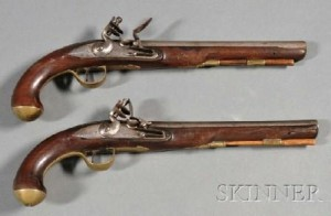Examples of 18th-century flintlock pistols with brass caps mounted on the end of the pistol grip